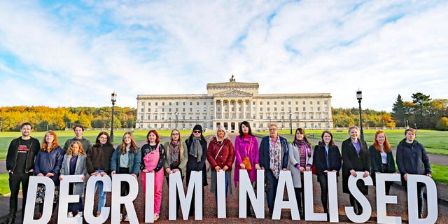 Pro-choice activists take part in a photo call in the grounds of Stormont Parliament, Belfast, Monday Oct. 21, 2019. Abortion is set to be decriminalized and same-sex marriage legalized in Northern Ireland as of midnight, bringing its laws in line with the rest of the U.K. (Niall Carson/PA via AP)