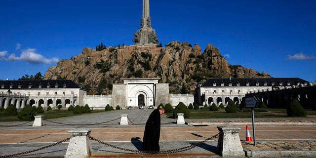 A friar walks in front of The Valley of the Fallen mausoleum near El Escorial, outskirts of Madrid.