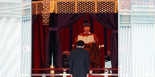 Japan's Emperor Naruhito speaks as Prime Minister Shinzo Abe bows during a ceremony to proclaim his enthronement to the world, called Sokuirei-Seiden-no-gi, at the Imperial Palace in Tokyo, Japan, Tuesday, Oct. 22, 2019. (Issei Kato/Pool Photo via AP)