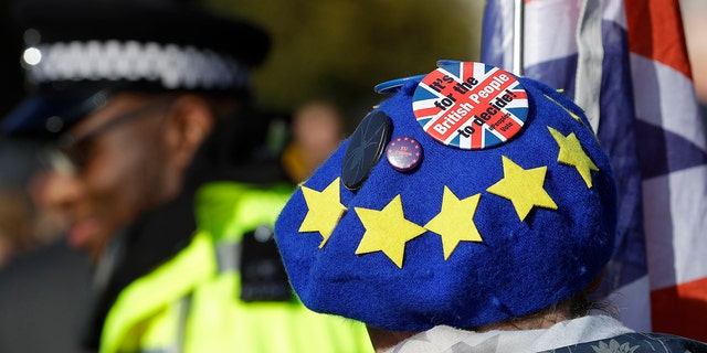 An anti-Brexit demonstrator wears a European Union patterned hat near Parliament in London, Tuesday, Oct. 22, 2019.