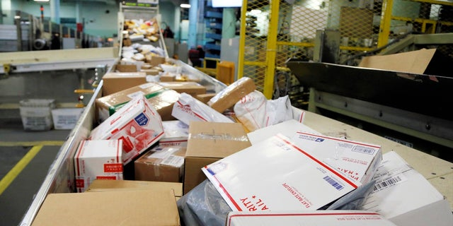 "In this Dec. 14, 2017, file photo, packages travel on a conveyor belt for sorting at the main post office in Omaha, Neb. The city of New York and the state of California sued the U.S. Postal Service Tuesday, Oct. 22, 2019, to stop tens of thousands of cigarette packages from being mailed from foreign countries to U.S. residents, saying the smugglers are engaging in ""cigarette tax evasion"" while postal workers look the other way. (AP Photo/Nati Harnik, File)"