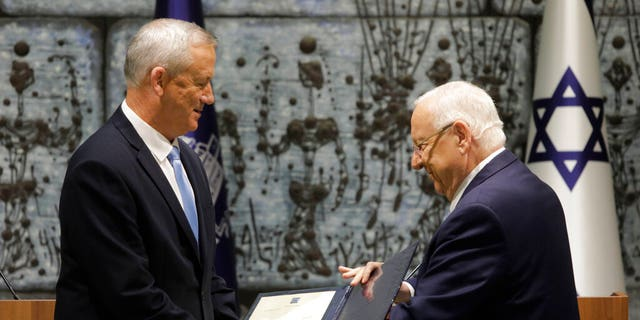 Israeli President Reuven Rivlin, right, hands a mandate to form new government to Blue and White Party leader Benny Gantz in Jerusalem, Wednesday, Oct. 23, 2019.