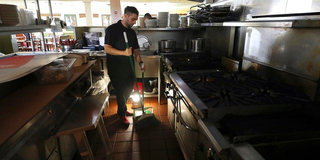 A power shutoff earlier this month leaves Salvador Espinosa with little to do but sweep up at Mary's Pizza Shack in Santa Rosa, Calif.