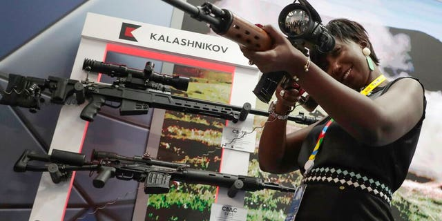 A visitor handles a sniper's rifle at an exhibition of Kalashnikov company weaponry on the sidelines of African countries at the Russia-Africa summit in the Black Sea resort of Sochi, Russia, Thursday, Oct. 24, 2019.