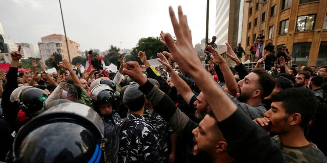 Lebanese riot policemen separates between anti-government protesters, left, and Hezbollah supporters, right during a protest in Beirut, Lebanon, Thursday, Oct. 24, 2019.