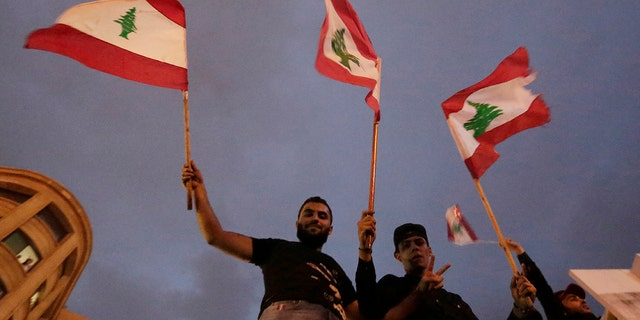 "Hezbollah supporters wave Lebanese national flag as Lebanese riot policemen separate them from anti-government protesters during a protest in Beirut, Lebanon, Thursday, Oct. 24, 2019. Lebanon's President Michel Aoun has told tens of thousands of protesters that an economic reform package put forth by the country's prime minister will be the ""first step"" toward saving Lebanon from economic collapse. (AP Photo/Hassan Ammar)"