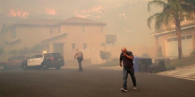 A resident covers his face as a wildfire approaches on Thursday in Santa Clarita, Calif. (AP Photo/Marcio Jose Sanchez)