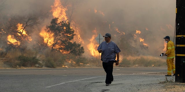 A man walks along Sierra Highway as flames from a wildfire overtake a hillside Thursday, Oct. 24, 2019, in Santa Clarita, Calif. The flames are fed by dry winds that are predicted to strengthen throughout the day across the region. (AP Photo/Marcio Jose Sanchez)