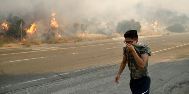 Brandon Mani covers his face from the smoke created by a wildfire as he walks along Highway 14 Thursday, Oct. 24, 2019, in Santa Clarita, Calif. (AP Photo/Marcio Jose Sanchez)