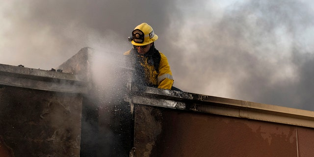 A structure firefighter works on the roof of a building during the Tick Fire in Santa Clarita, Calif., on Thursday, Oct. 24, 2019. (Associated Press)