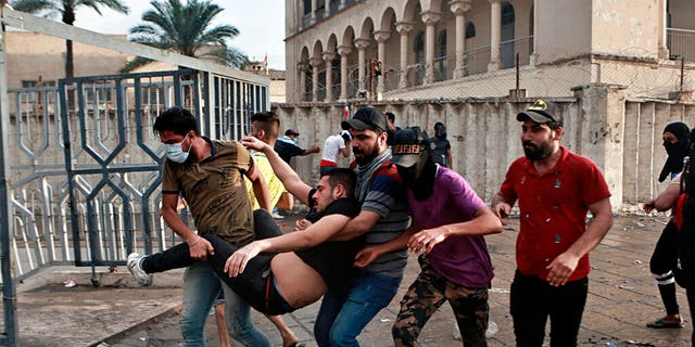 An injured protestor is rushed to a hospital during a demonstration in central Baghdad. Iraqi police fired live shots into the air as well as rubber bullets and dozens of tear gas canisters on Friday to disperse thousands of protesters