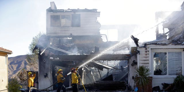 Firefighters try to put out a residence fire caused by a wildfire Friday, Oct. 25, 2019, in Santa Clarita, Calif. An estimated 50,000 people were under evacuation orders in the Santa Clarita area north of Los Angeles as hot, dry Santa Ana winds howling at up to 50 mph (80 kph) drove the flames into neighborhoods(AP Photo/Marcio Jose Sanchez)