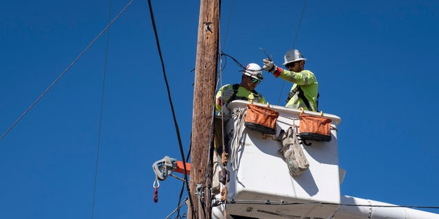 SoCal Edison crews replace power lines that were damaged from the Tick Fire, Thursday, Oct. 25, 2019, in Santa Clarita, Calif. An estimated 50,000 people were under evacuation orders in the Santa Clarita area north of Los Angeles as hot, dry Santa Ana winds howling at up to 50 mph (80 kph) drove the flames into neighborhoods (AP Photo/ Christian Monterrosa)from the Tick Fire, Thursday, Oct. 25, 2019, in Santa Clarita, Calif. An estimated 50,000 people were under evacuation orders in the Santa Clarita area north of Los Angeles as hot, dry Santa Ana winds howling at up to 50 mph (80 kph) drove the flames into neighborhoods (AP Photo/ Christian Monterrosa)