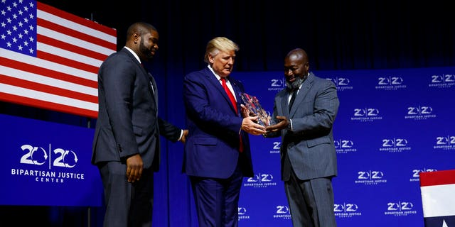 "President Donald Trump is awarded the Bipartisan Justice Award by Matthew Charles, right, one of the first prisoners released by the First Step Act, during the ""2019 Second Step Presidential Justice Forum"" at Benedict College, Friday, Oct. 25, 2019, in Columbia, S.C."