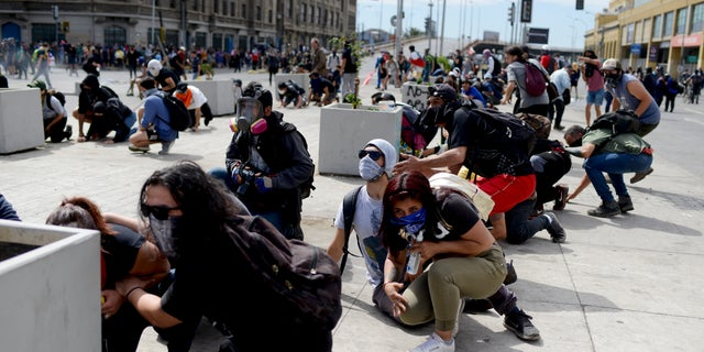 Anti-government protesters take cover just around the corner from the Congress building, during clashes with police in Valparaiso, Chile, Friday, Oct. 25, 2019. A new round of clashes broke out Friday as demonstrators returned to the streets, dissatisfied with economic concessions announced by the government in a bid to curb a week of deadly violence.(AP Photo/Matias Delacroix)