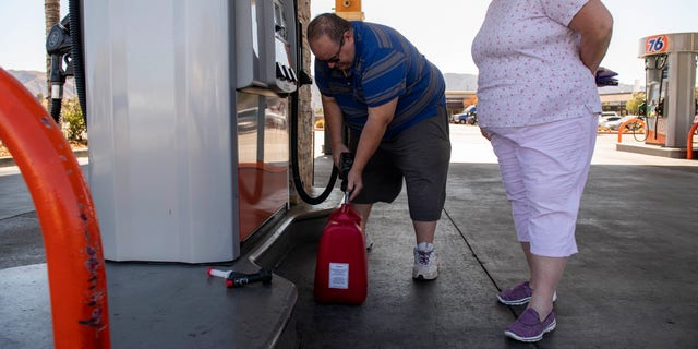 Richard and Sheri Rose fill a plastic jerry can to power their generator while the power remains shut off from the Tick Fire, Thursday, Oct. 25, 2019, in Santa Clarita, Calif. An estimated 50,000 people were under evacuation orders in the Santa Clarita area north of Los Angeles as hot, dry Santa Ana winds howling at up to 50 mph (80 kph) drove the flames into neighborhoods (AP Photo/ Christian Monterrosa)
