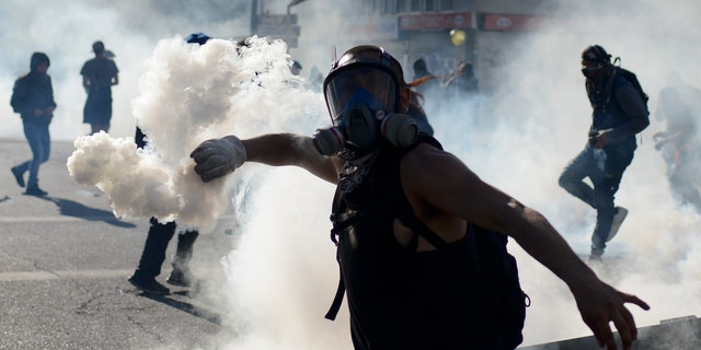 An anti-government protester returns a tear gas canister to police during clashes in Valparaiso, Chile, Friday, Oct. 25, 2019. A new round of clashes broke out Friday as demonstrators returned to the streets, dissatisfied with economic concessions announced by the government in a bid to curb a week of deadly violence.(AP Photo/Matias Delacroix)