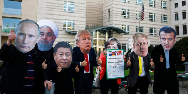 Protestors with masks of world leaders protest in front of the United States embassy, demanding a new nuclear agreement with Iran to avoid a possible armed conflict at the mideast region, in Berlin, Saturday, Oct. 26, 2019.