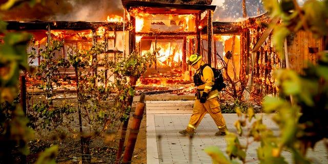 Woodbridge firefighter Joe Zurilgen passing a burning home as the Kincade Fire raged in Healdsburg, Calif., on Sunday.