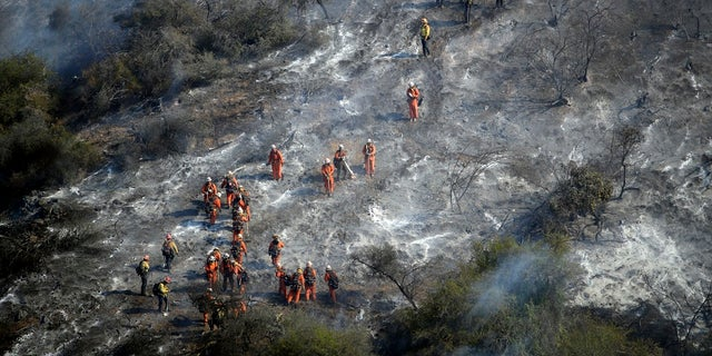 Hand crews work a wildfire-damaged hillside as the Getty fire burns on Mandeville Canyon, Oct. 28, 2019, in Los Angeles. (AP Photo/Marcio Jose Sanchez)