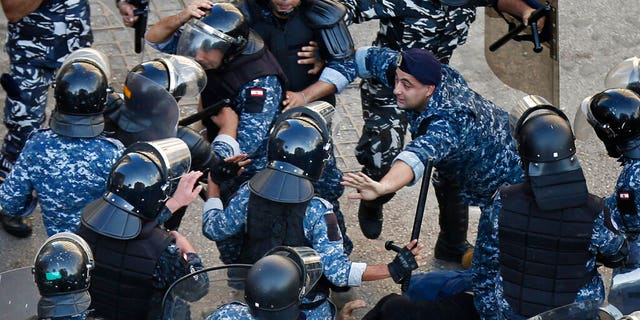 A riot police officer, center right, stops other policemen from beating a protester who lies on the ground, after clashes erupted between an anti-government protesters and Hezbollah supporters near the government palace, in Beirut, Lebanon, Tuesday, Oct. 29, 2019.