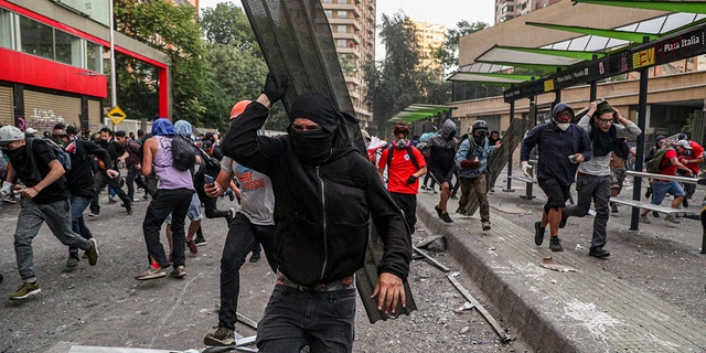 Anti-government protesters run from police in Santiago, Chile, Tuesday, Oct. 29, 2019.