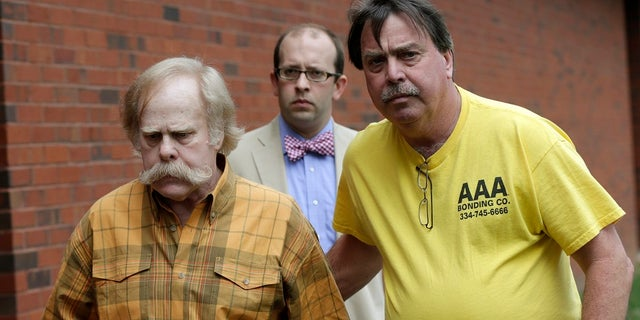US News Harvey Updyke, left, leaves the Lee County Justice Center in Opelika, Ala., with his bail bondsman and his attorney in this 2013 photo. (AP Photo/Dave Martin, File)