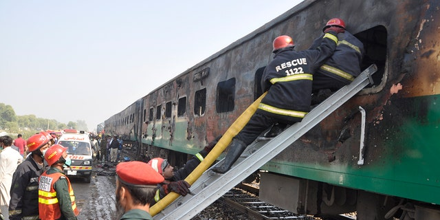 Rescue workers look for survivors following a train damaged by a fire in Liaquatpur, Pakistan, Thursday, Oct. 31, 2019. A massive fire engulfed three carriages of the train traveling in the country's eastern Punjab province