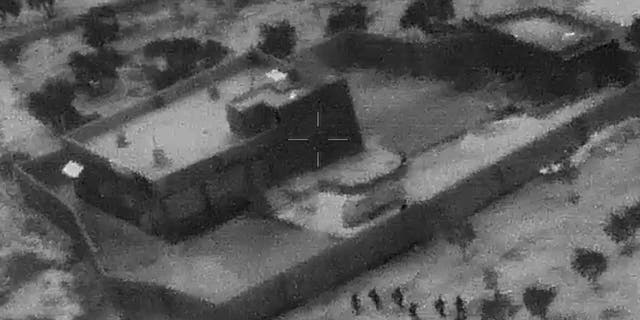 This image from video released by the Department of Defense on Wednesday, Oct. 30, 2019, and displayed at a Pentagon briefing, shows U.S. Special Forces, figures at lower right, moving toward compound of Islamic State leader Abu Bakr al-Baghdadi on Saturday, Oct. 26, 2019. (Department of Defense via AP)