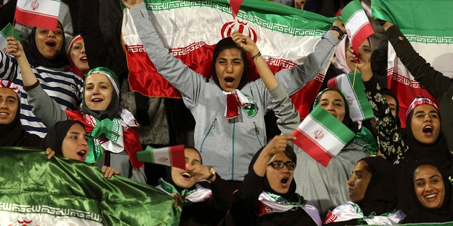 FILE: Iranian women cheer as they wave their country's flag after authorities, in a rare move, allowed a select group of women into Azadi stadium to watch a friendly soccer match between Iran and Bolivia, in Tehran, Iran.