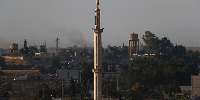 In this print taken from a Turkish side of a limit between Turkey and Syria, in Akcakale, Sanliurfa province, southeastern Turkey, a city of Tel Abyad can be seen inside Syria, Saturday, Oct. 12, 2019. (AP Photo/Lefteris Pitarakis)