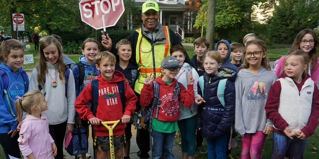 Alec Childress, 80, poses with school children he helps as a crossing guard in Illinois. On Thursday, his birthday, they surprised him with a big celebration to thank him for brightening their day every morning.