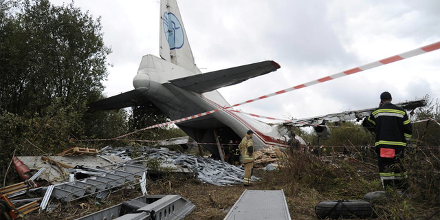Members of emergency services work at the site of the Antonov-12 cargo airplane emergency landing in Lviv region, Ukraine Oct. 4, 2019.
