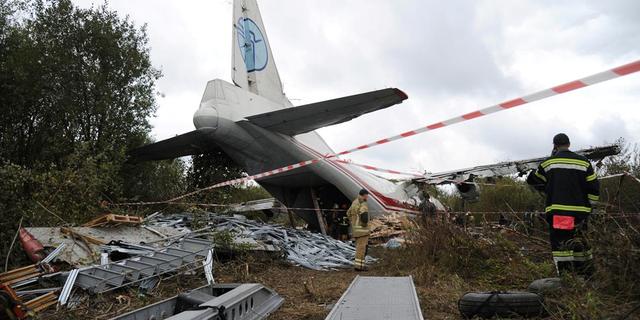 Members of emergency services work at the site of the Antonov-12 cargo airplane emergency landing in Lviv region, Ukraine Oct. 4, 2019.