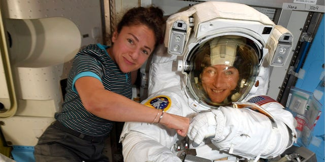 Astronauts Christina Koch, right, and, Jessica Meir pose on the International Space Station. The first all-female spacewalk is back on, six months after a flap over spacesuits led to an embarrassing cancellation. (NASA via AP)