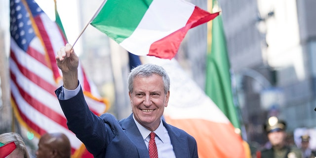 New York City Mayor Bill de Blasio waves to people along the street while holding an Italian flag. (Photo by Ira L. Black/Corbis via Getty Images)