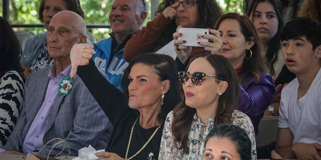 A viewer in the stands at the Columbus Day Parade gives a thumb down, while others boo and whistle as Mayor Bill de Blasio participates, Monday Oct. 14, 2019, in New York. (AP Photo/Bebeto Matthews)