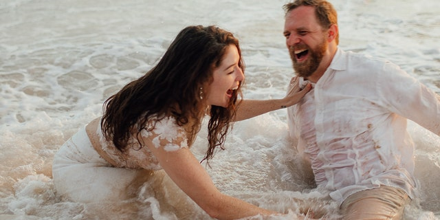 A Texas couple's beachside wedding photos didn't turn out quite the way they expected after an ocean tide caused them to tumble, ruining the bride's dress in the process.