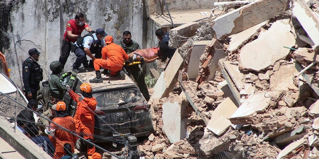 Firefighters rescue a woman from a building that collapsed in Fortaleza on Tuesday. (Kleber Goncalves/Futura Press via AP)