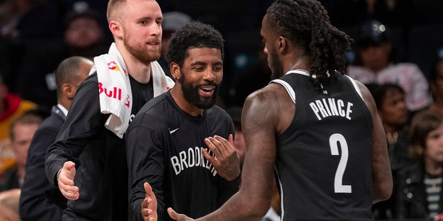 Brooklyn Nets guard Dzanan Musa, left, and /guard Kyrie Irving, center, greet forward Taurean Prince (2) as he comes into the bench during a timeout in the first half of an exhibition NBA basketball game against the Sesi/Franca Basketball Club, Friday, Oct. 4, 2019, in New York. (AP Photo/Mary Altaffer)
