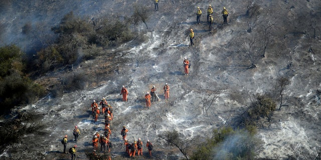 Hand crews work a wildfire-damaged hillside as the Getty fire burns on Mandeville Canyon, Oct. 28, 2019, in Los Angeles.