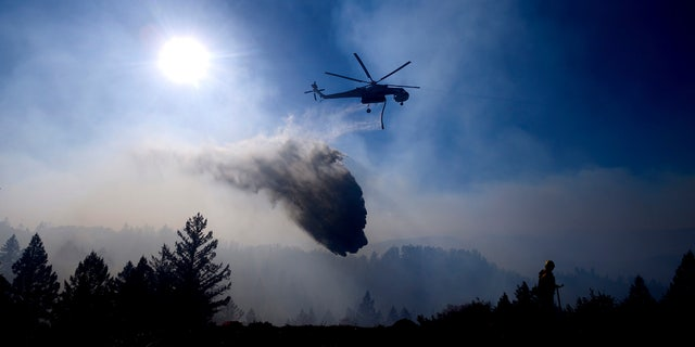 A helicopter drops water while battling the Kincade Fire near Healdsburg, Calif., on Tuesday, Oct. 29, 2019. Millions of people have been without power for days as fire crews race to contain two major wind-whipped blazes that have destroyed dozens of homes at both ends of the state: in Sonoma County wine country and in the hills of Los Angeles. (Associated Press)
