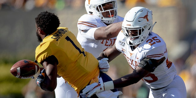 Texas defensive back B.J. Foster (25) shoves West Virginia wide receiver T.J. Simmons (1) during an NCAA college football game on Saturday, Oct. 5, 2019, in Morgantown, W.Va. (Nick Wagner/Austin American-Statesman via AP)