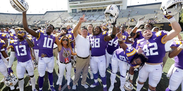 LSU head coach Ed Orgeron, center, celebrates with his players after defeating Vanderbilt in an NCAA college football game Saturday, Sept. 21, 2019, in Nashville, Tenn. LSU won 66-38. (AP Photo/Mark Humphrey)