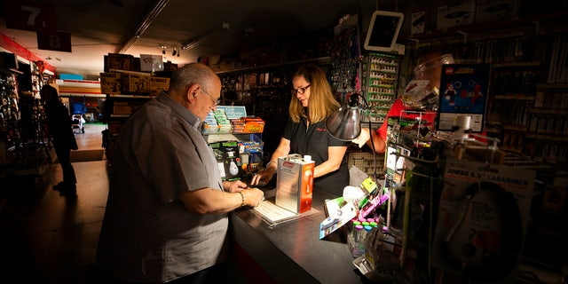 Tom Hyde, left, buys a can of fuel for his Coleman camp stove from Kim Scheffer at a Village True Value Hardware store in Santa Rosa, Calif., Wednesday, Oct. 9, 2019.
