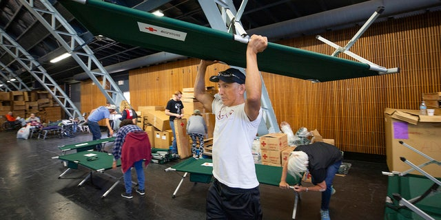 In this Sunday, Oct. 27, 2019, photo, volunteer Alejandro Pablo carries a newly built cot to an evacuee in need at a Red Cross shelter set up for wildfire evacuees at the Sonoma County Fairgrounds in Santa Rosa, Calif.