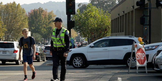 A Lafayette police officer stops traffic for a schoolboy at an intersection that has lost power Monday, Oct. 28, 2019, in Lafayette, Calif.