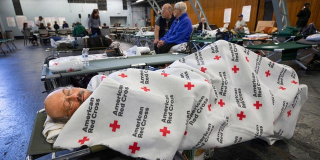 In this Sunday, Oct. 27, 2019, photo, Jim Keefauver rests at a Red Cross shelter set up for wildfire evacuees at the Sonoma County Fairgrounds in Santa Rosa, Calif., after evacuating his Santa Rosa home in the morning.