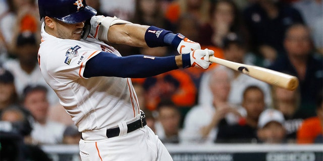 Houston Astros' Carlos Correa hits a walk-off home run against the New York Yankees during the 11th inning in Game 2 of baseball's American League Championship Series Sunday, Oct. 13, 2019, in Houston. (AP Photo/Matt Slocum)