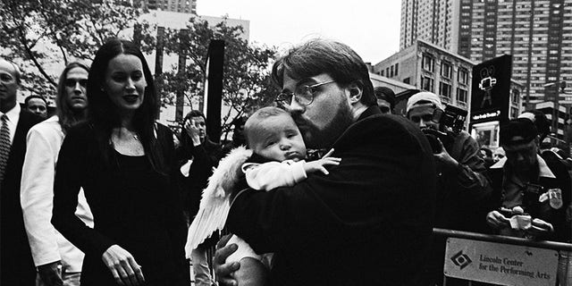 "American director and screenwriter Kevin Smith holds daughter Harley Quinn dressed in angel wings on the red carpet at the premiere of this film ""Dogma"" in October 1999 in New York City, New York. The controversial film, a religious comedy, was protested by the Catholic League upon its release."